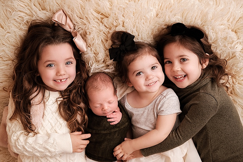 3 children posing together with newborn brother