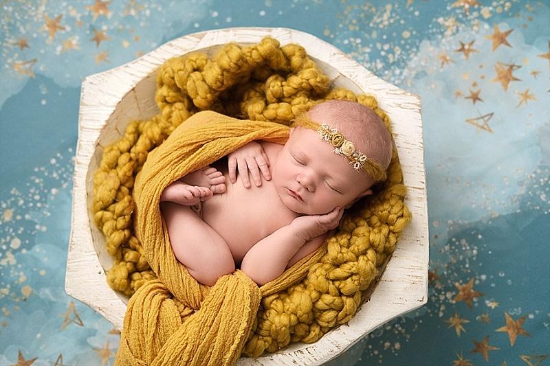 baby girl on yellow blanket