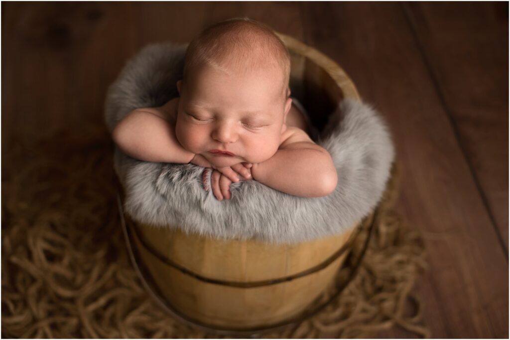 newborn boy in brown bucket southeast michigan newborn session
