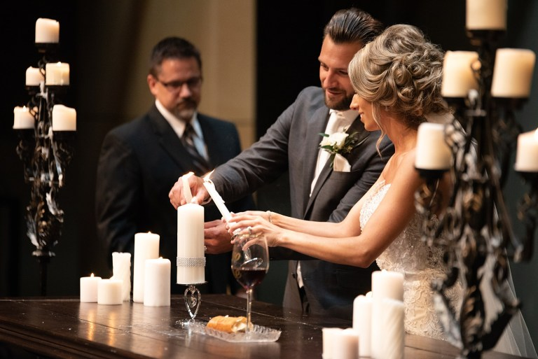 couple lighting unity candle in a church wedding photography Katie Anton