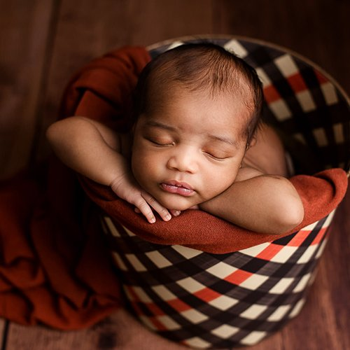 adorable black baby in a basket newborn photography