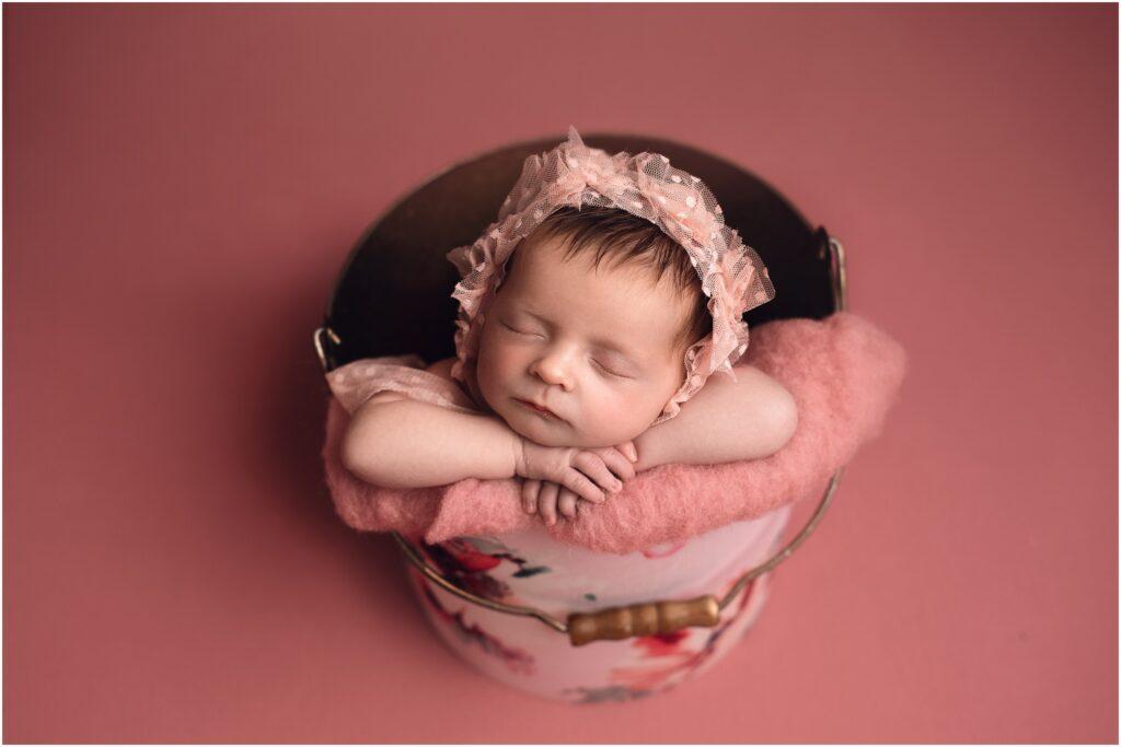 newborn girl in a pink bucket