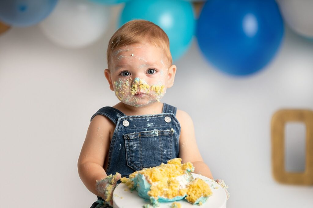 cute boy covered in cake