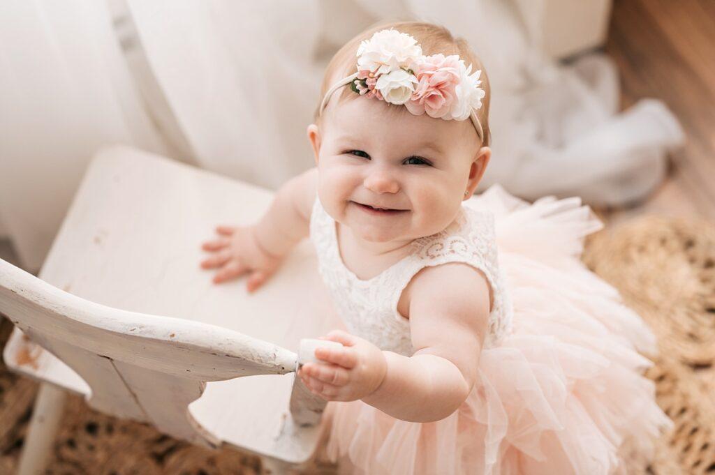 little girl smiling standing against chair
