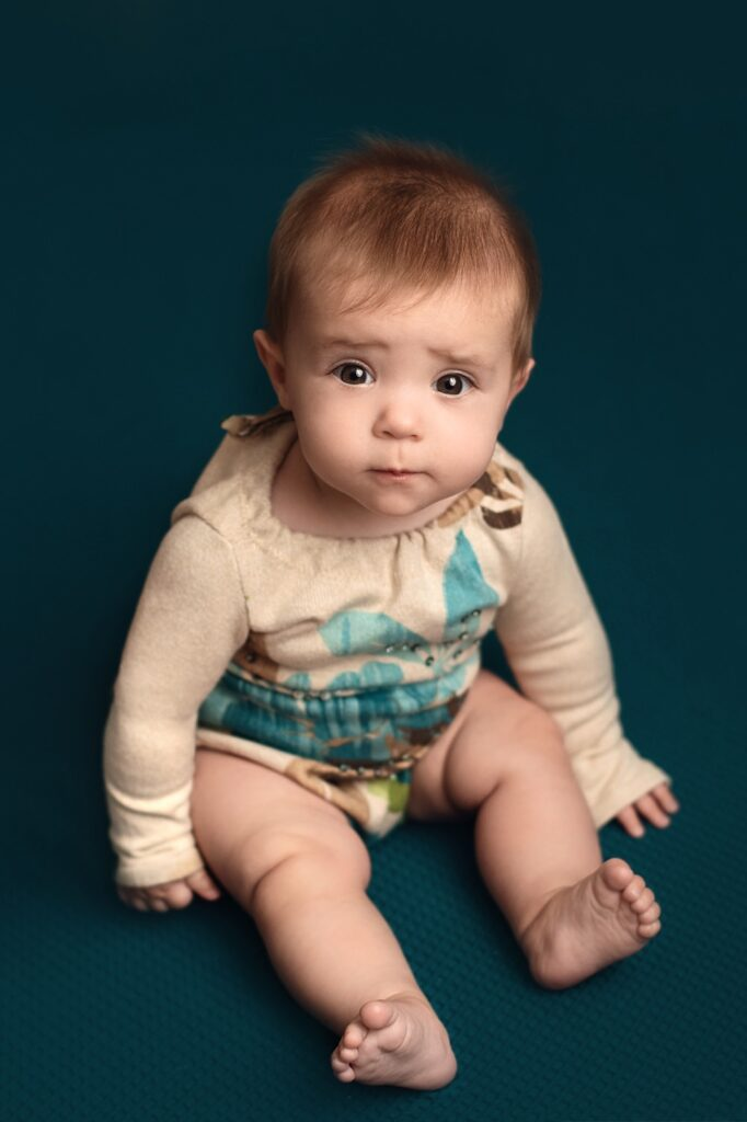 sitter girl in teal and brown romper