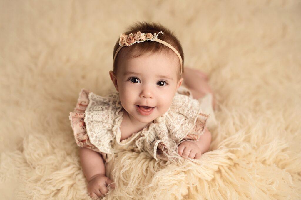 6 month girl in beige romper