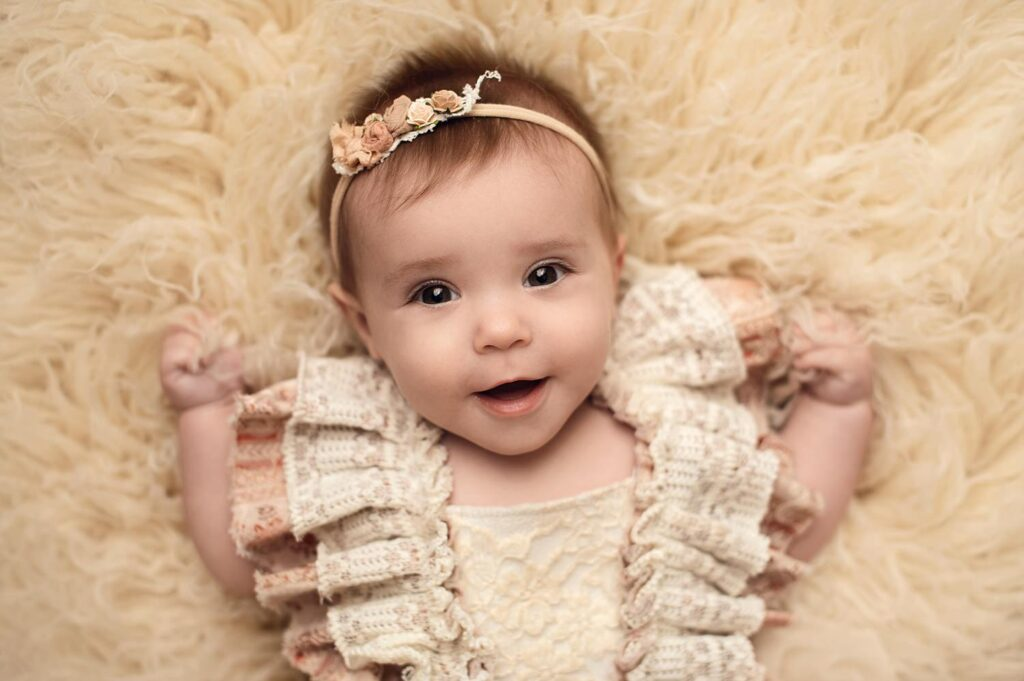 6 month girl on back in beige romper
